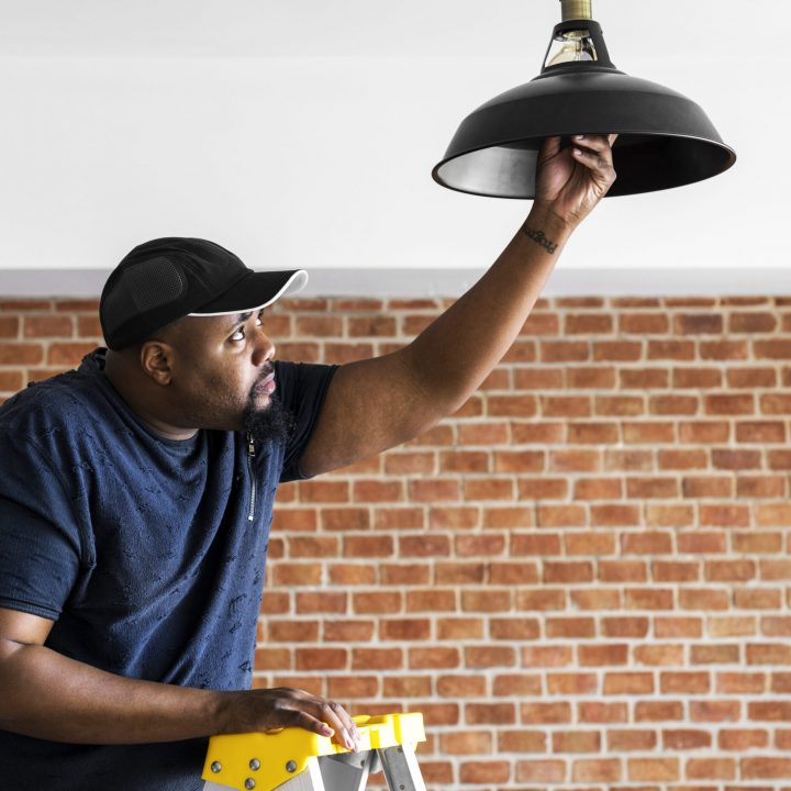 Black guy installing light bulb
